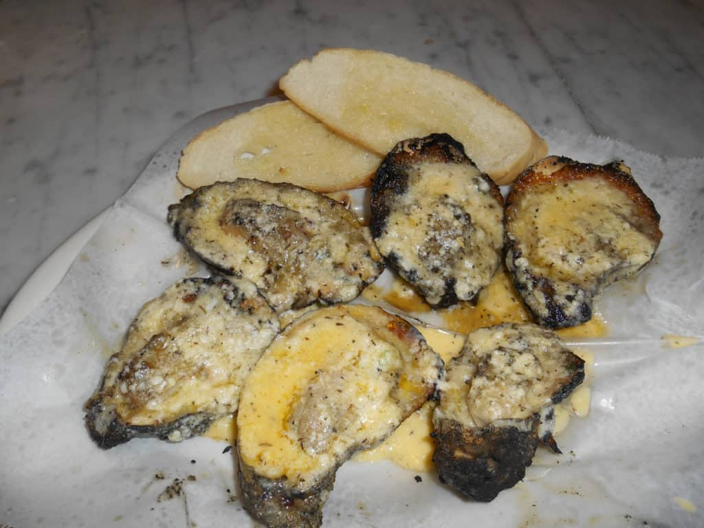 Charbroiled oysters stuffed with butter and parmesan cheese